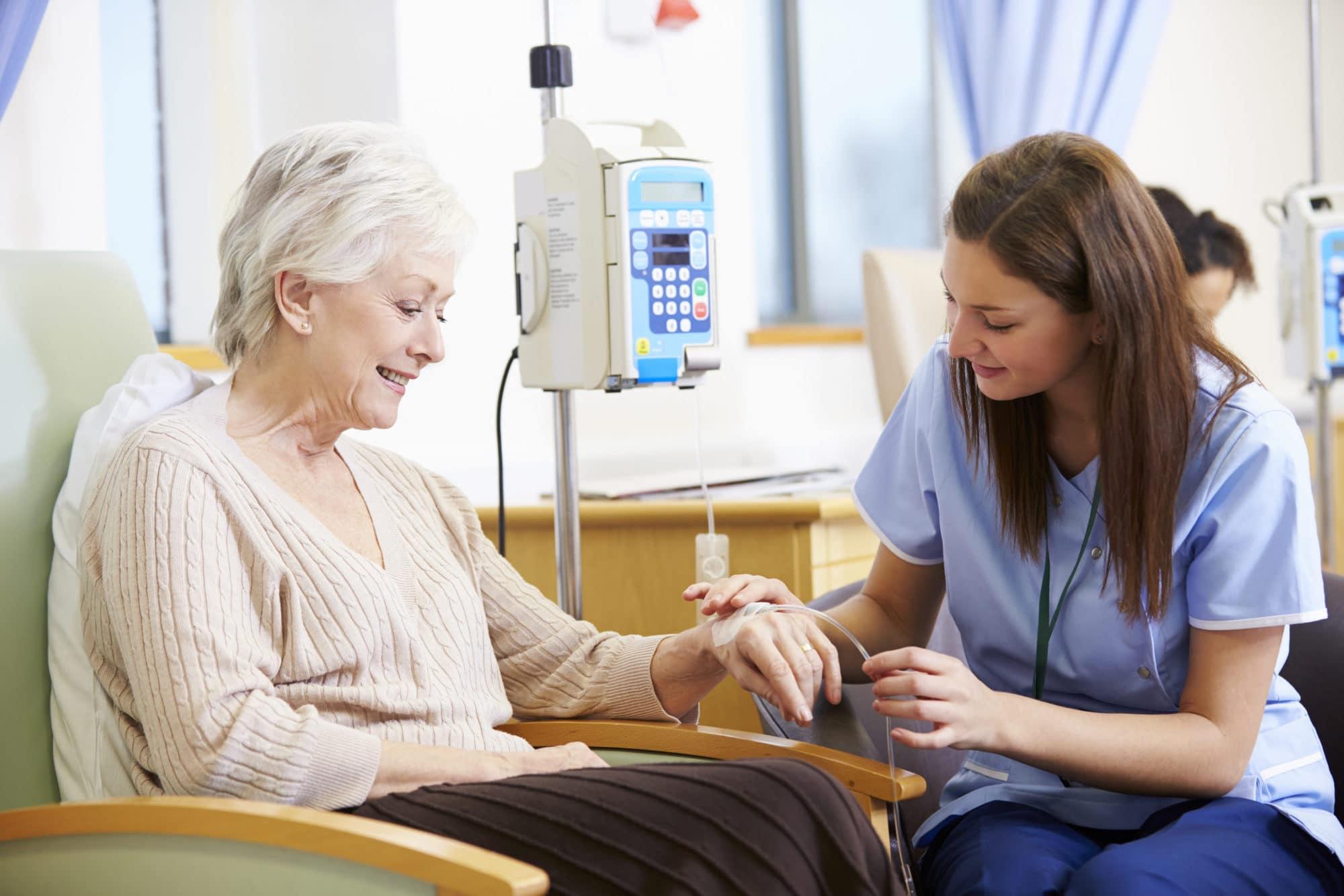 Senior Woman Undergoing Chemotherapy With Nurse