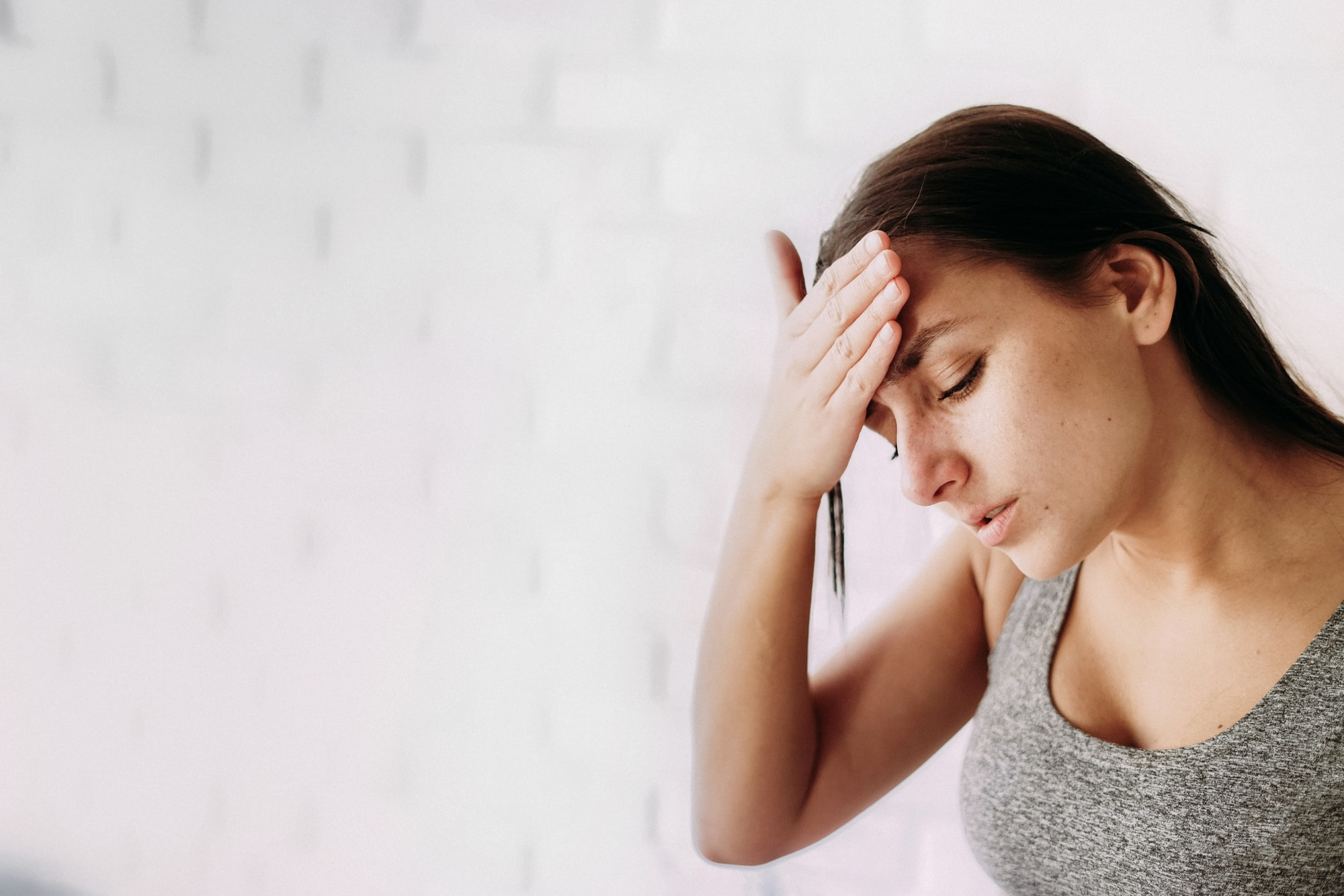 A close-up portrait of a young woman standing sad and holding his head in his hand and a white brick wall in the background. Headache and worries about illness, unemployment, temperature. Copyspace