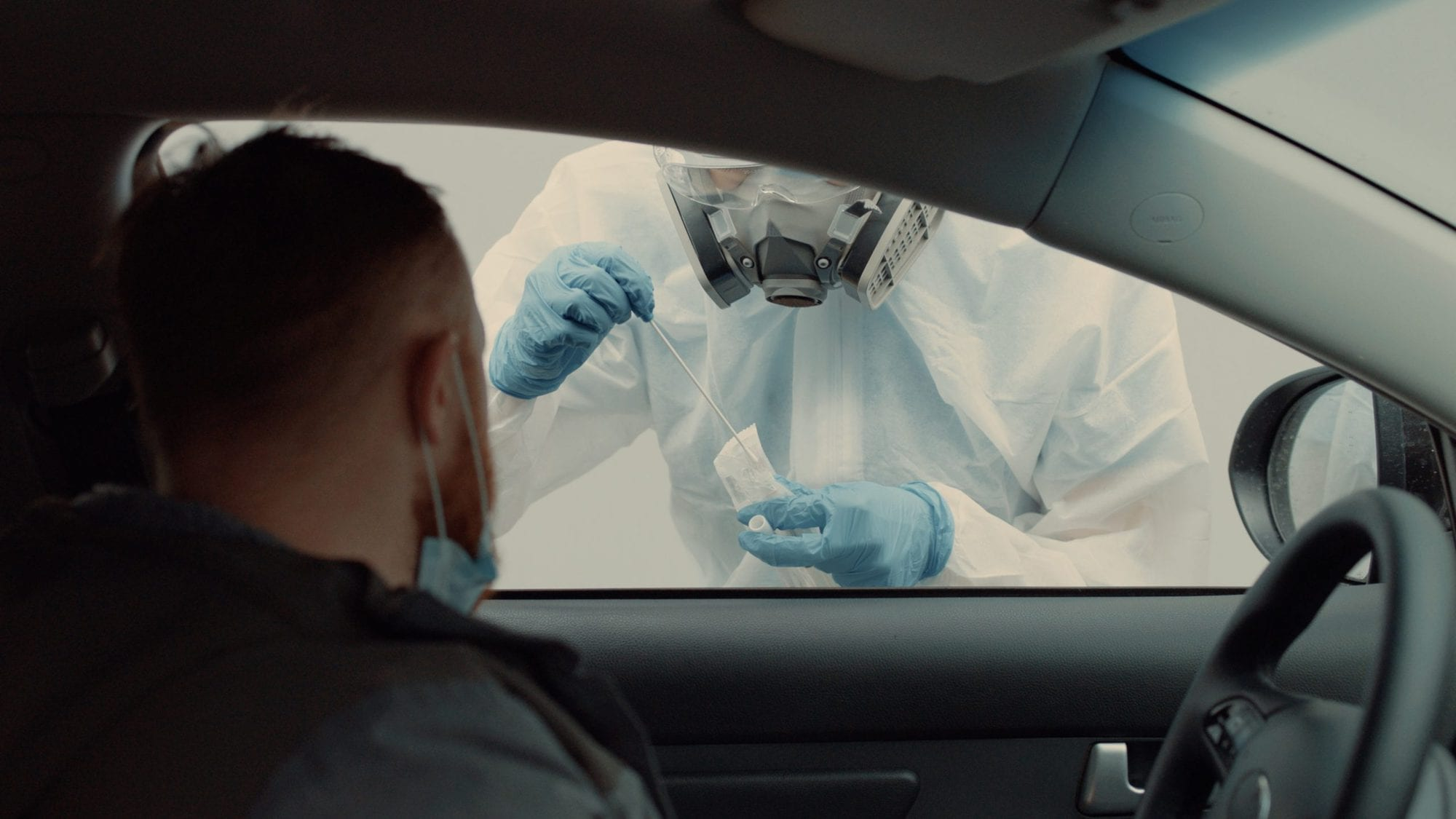Patient is being tested in his vehicle on adrive-through coronavirus COVID-19 testing location. Pandemic, infection