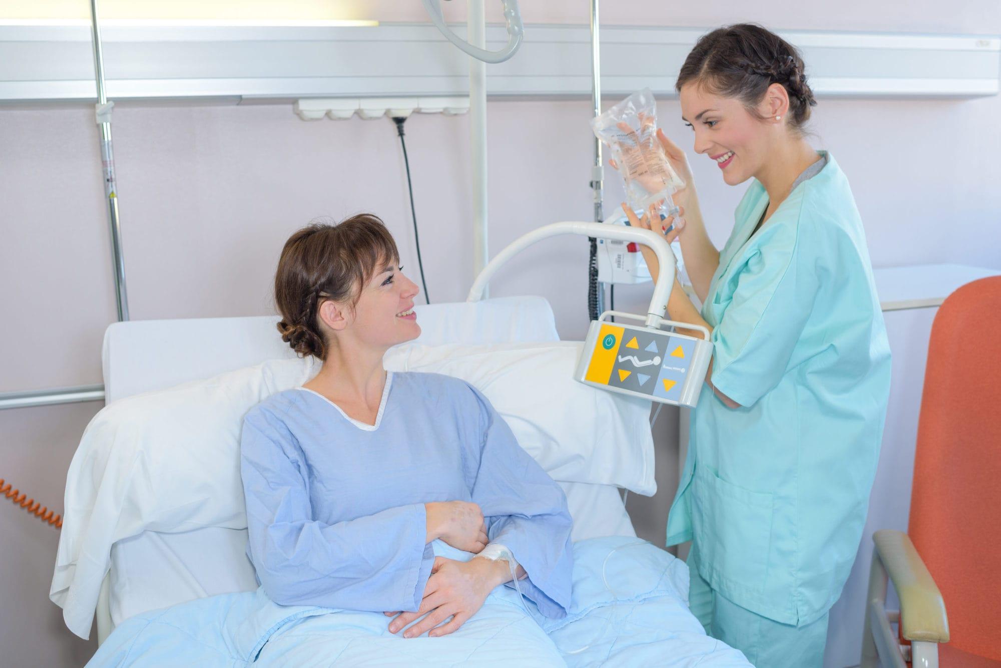 Nurse changing patient's drip bag